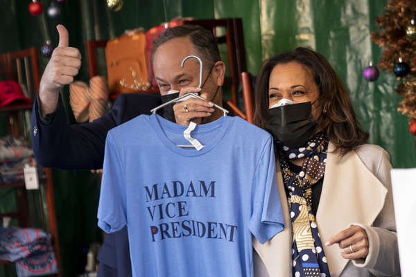 Kamala Harris smiles while holding up a tshirt with Madam Vice President
