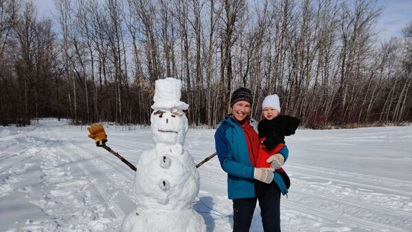 Young woman holds baby in front of snowman
