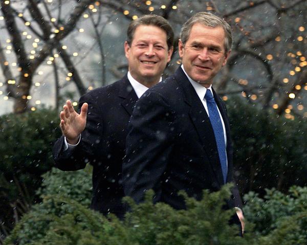 Al Gore waves as he walks with George W Bush