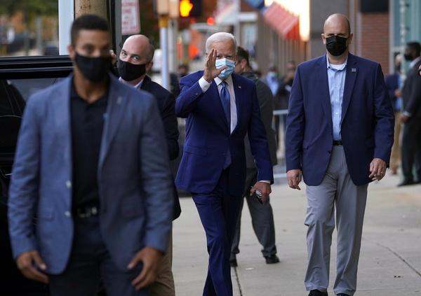 Surrounded by Secret Service, U.S. Democratic presidential candidate Joe Biden waves as he walks to his motorcade vehicle in downtown Wilmington, Delaware, U.S