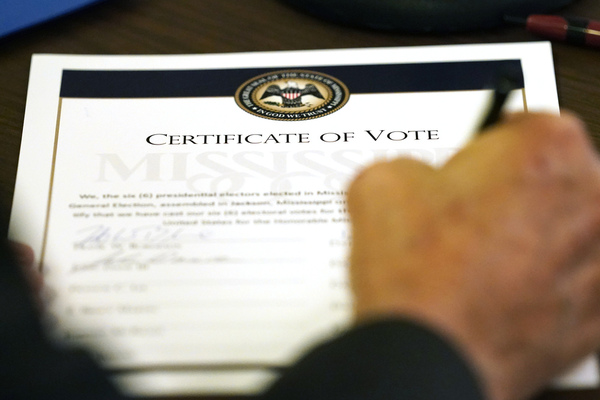 A person signs a paper with 'certificate of vote' written on it