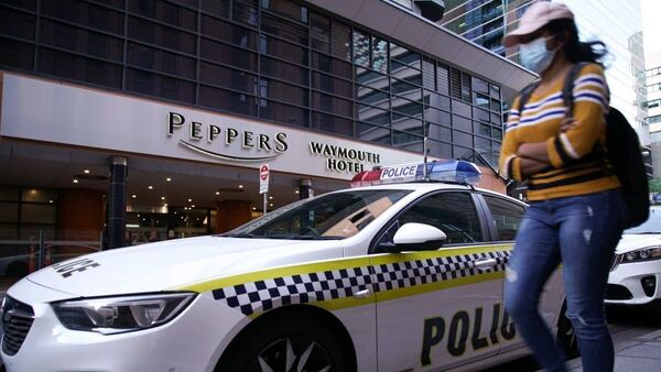 A woman in a mask walks past a police car parked outside Peppers hotel in Adelaide.