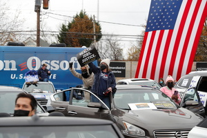Supporter of Democratic U.S. Senate candidates Rev. Raphael Warnock and Jon Ossoff attend a drive-in campaign rally with U.S. President-elect Joe Biden