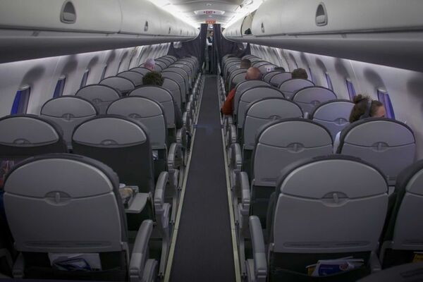 A view of the inside of a plane, looking down the aisle. There is a total of 5 people sitting in various seats