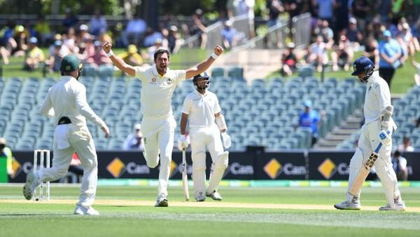 Mitchell Starc runs with his arms up on a cricket field.