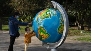 A child wearing a mask touches a large sculpture of a globe