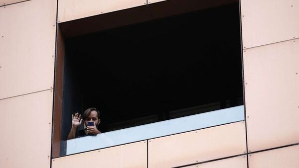 A man waves while holding his phone from a window of a high building.