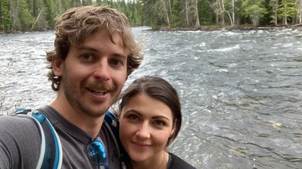 A man and a woman smile at the camera as they stand in front of a river.