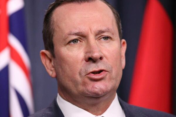 A tight head shot of WA Premier Mark McGowan speaking during a media conference indoors with flags behind him.