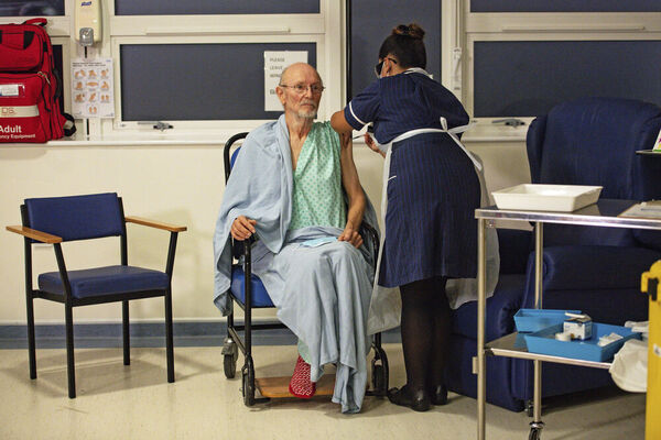 A man sits in a wheelchair as a woman stands over him and administers a vaccine in a hospital setting.