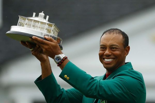 Tiger Woods wears his green jacket holding the winning trophy after the final round for the Masters golf tournament Sunday.