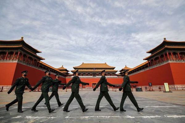 Soldiers wearing protective face masks march past the closed entrance gates to the Forbidden City.