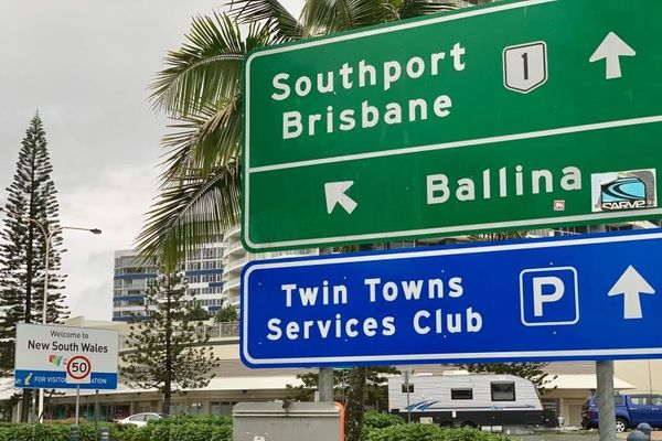 A road sign indicates the border between Queensland and New South Wales