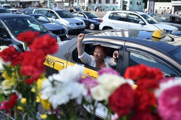 Une femme lève le poing depuis un taxi devant le site où un manifestant est décédé hier soir à Minsk le 11 août. Sergei GAPON / AFP