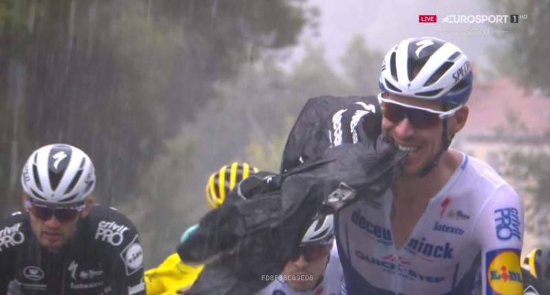 Los ciclistas se protegen ante la lluvia que cae sobre el pelotón del Tour