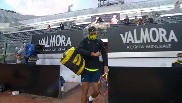 Rafa Nadal, enmascarado. Viste de amarillo lima.