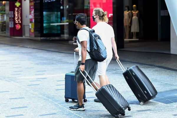 People carrying luggage wear face masks as they make their way through the CBDB of Brisbane.