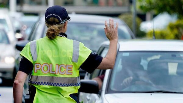 A police officer stops a driver at a checkpoint at Coolangatta on the Queensland - New South Wales border