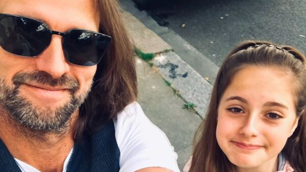 A father (left) takes a selfie with his daughter (right).