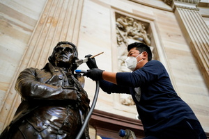 Gompo Yarmolinsky with the Architect of the Capitol cleans dust from the statue of Thomas Jefferson in the Capitol Rotunda after supporters of U.S. President Donald Trump stormed the U.S. Capitol