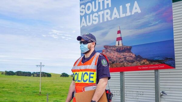 a masked police officer stands in front of the 'welcome to south australia' sign