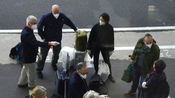 a group of masked travellers stand outside a hotel with their bags.