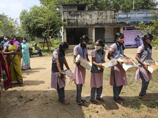 A line of girls hold boxes of packaged food and sweets. They wear uniforms and stand in front of a building, with older women to the left hand side.