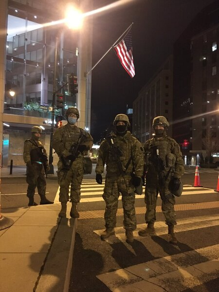 Four people are seen in army gear with guns strapped to their chests. An American flag is above them, and it is dark out.