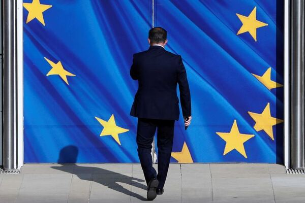 A man in a suit walks toward double doors emblazoned with the EU flag.