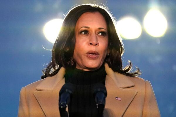 Vice President-elect Kamala Harris speaks during a COVID-19 memorial. She wears a camel coat with a US flag pinned to the lapel. Her hair is down, the sky behind her is mostly dark but two lights flare behind her head.