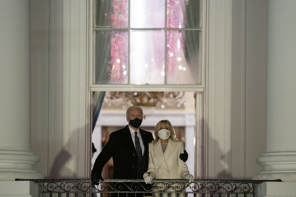 Joe Biden, with his arm around wife Jill Biden, stand on a balcony as they both look up to the sky. A reflection of fireworks is visible in the window above them