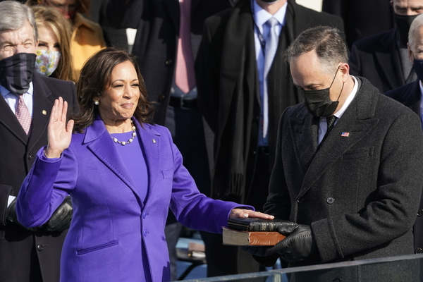 Kamala Harris, resplendent in purple, smiles proudly as she holds one hand up and the other on a stack of two bibles