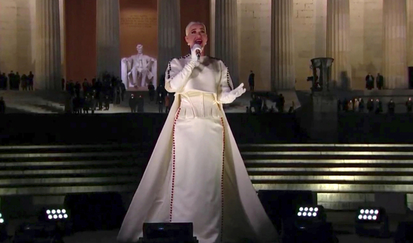 Katy Perry, in a white gown and gloves, sings into a microphone while standing on the steps of the Lincoln Memorial