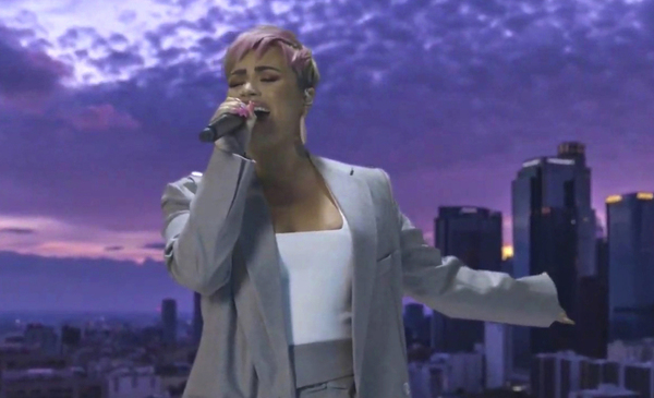 Demi Lovato, in a grey suit and pink cropped hair, sings into a microphone with her eyes closed. The sky behind her appears purple.