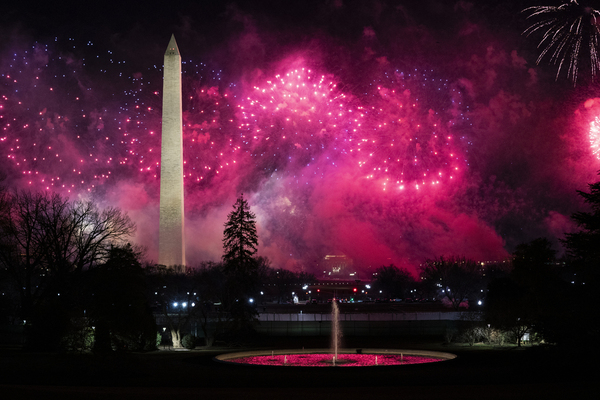 Pink fireworks explode across the night sky. The Washington Monument is visible, and the outlines of trees and city lights