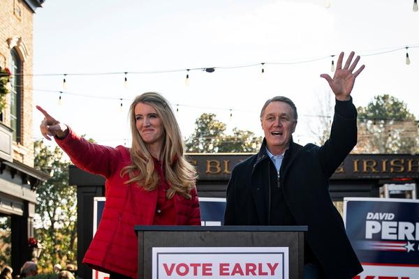 Senator Kelly Loeffler (R-GA) and Senator David Perdue (R-GA), wave during a campaign event.