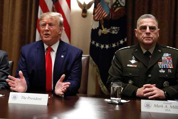 Donald Trump sits next to General Mark Milley