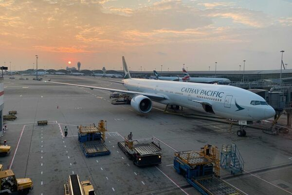 A Cathay Pacific plane is parked at a gate with its luggage hold open, at Hong Kong International Airport.