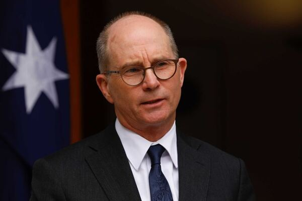 A portrait of a balding man wearing glasses, a suit and a dark tie.