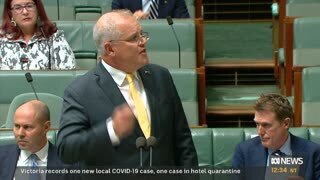 Scott Morrison looks to the right as he gesticulates while talking. He wears a dark suit and a yellow tie.