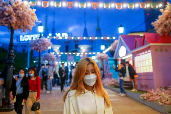 A young woman in a face mask walks through a street strung with fairy lights in Seoul