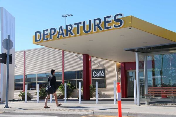 A person wearing black walks into a building with departures written on it in capital letters.