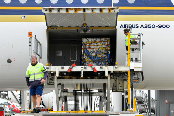 Two men are seen standing next to an airbus plane, one of them stands near a crate that contains vaccines.