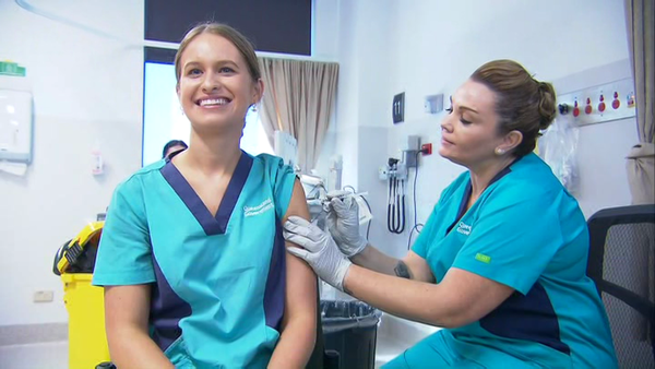 A smiling nurse is given a needle in the arm
