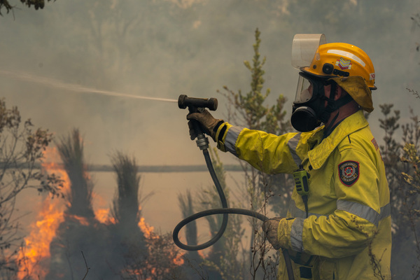 A firefighter is seen pointing a hose at a fire out of the shot. He wears yellow gear including a hard hat and a black mask.