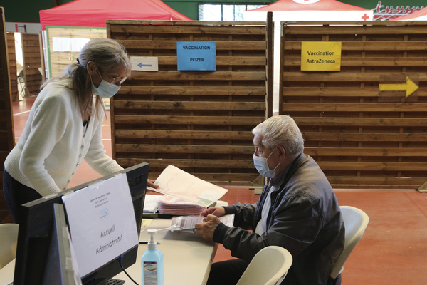 A person hands over paperwork at a vaccine hub reception desk