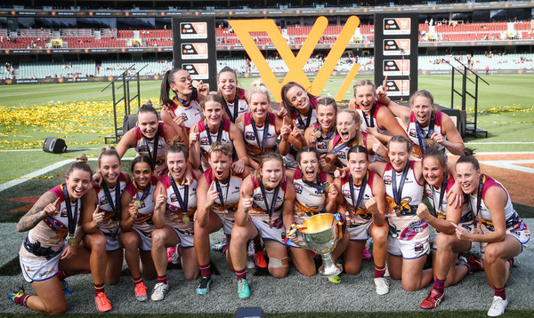 Brisbane Lions AFLW players celebrate with the premiership trophy.