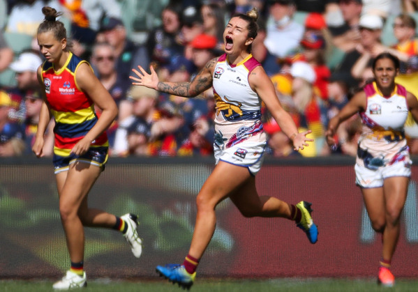A Brisbane Lions AFLw player stretches her arms out as she celebrates a goal.