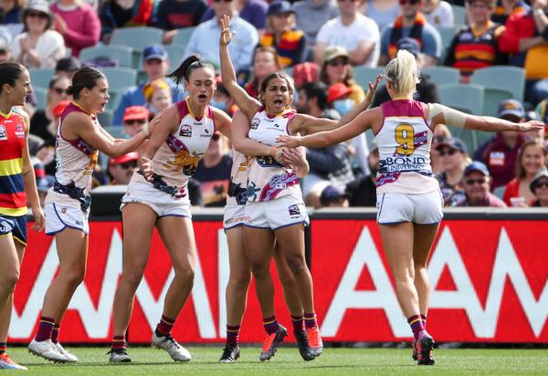 Five Brisbane Lions AFLW players celebrate a goal.
