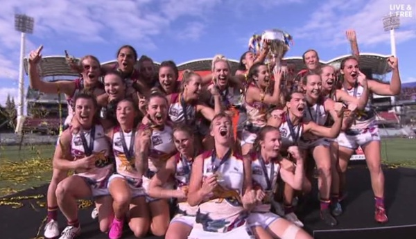 The Brisbane Lons AFLW players celebrate with the premiership trophy.